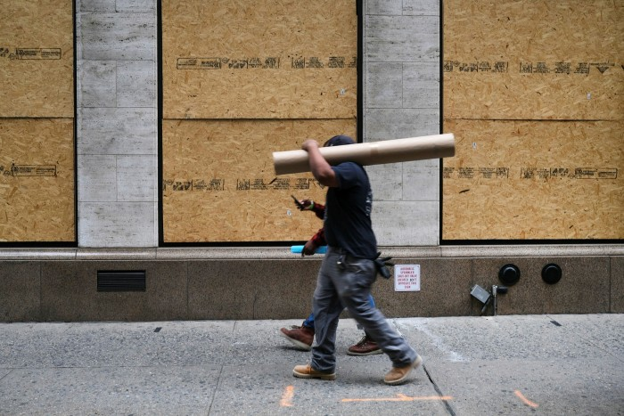 People walk past a boarded up business in New York. Biden's stimulus plan is designed to boost America's social safety net and ensure low and middle-income households can make it to the end of the Coronavirus crisis without suffering lasting damage