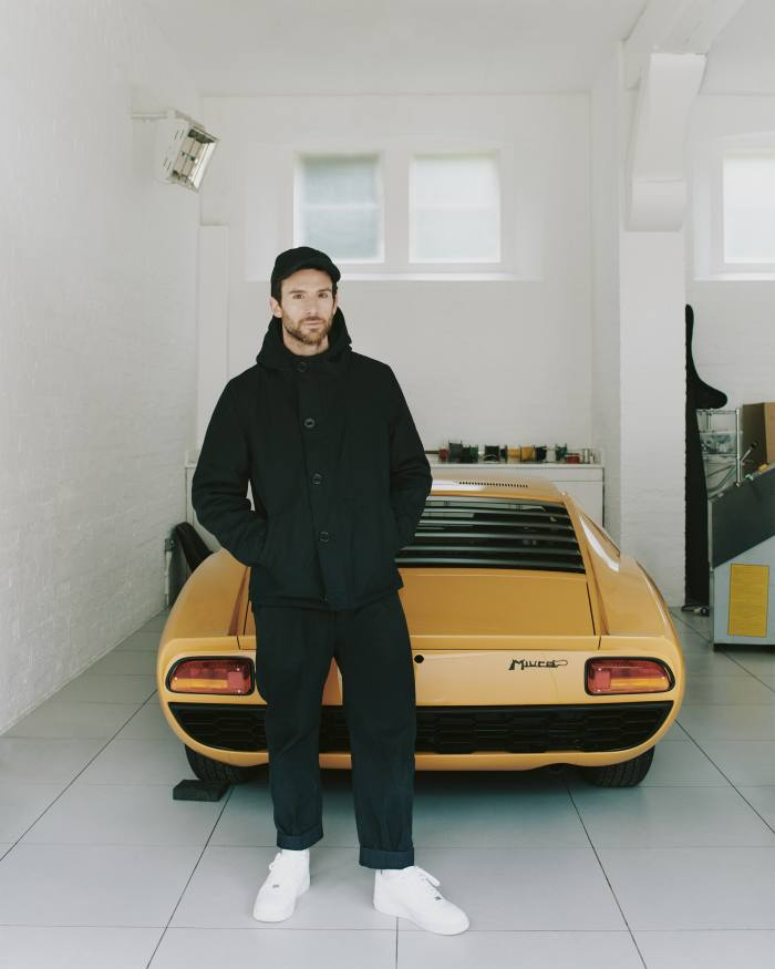 Berryman in his garagewith his 1960s Lamborghini Miura P400. He wears Applied Art Forms CM1-1 hooded deck jacket, €790, and cargo trousers, €390