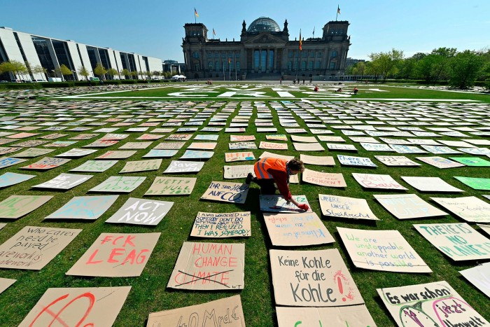 """A """"Fridays for Future"""" activist places hand-painted posters calling for climate change action on the meadow in front of the Reichstag building, Berlin, in 2020"""
