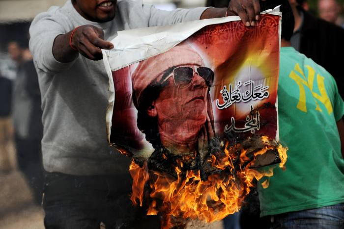 A protester burns a poster of Libyan dictator Muammer Gaddafi in Benghazi in March 2011