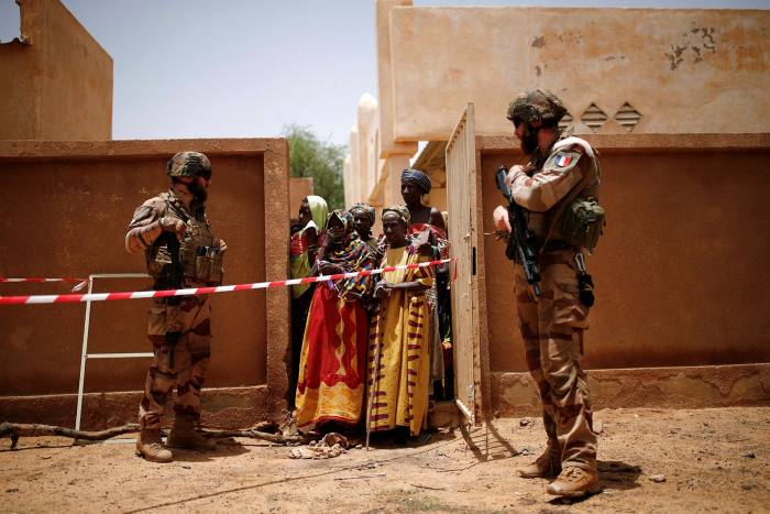 Local women and children queue for a medical aid operation during the Operation Barkhane in Ndaki, Mali. The French military operation is tasked with fighting al-Qaeda and Isis in the semi-desert south of the Sahara