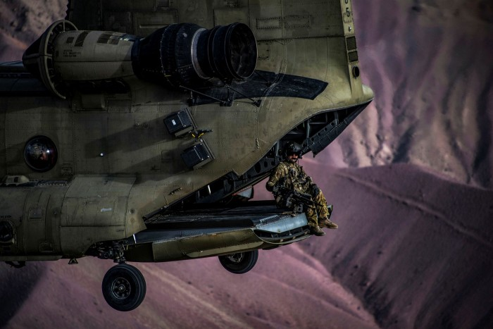 A US Army Chinook helicopter flight engineer sits on the ramp during a training exercise at Bagram Airfield, Afghanistan