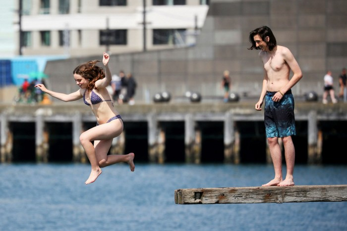 Beachgoers dive into Wellington Harbour on Sunday. Life in the New Zealand capital is near normal while Auckland endures another lockdown