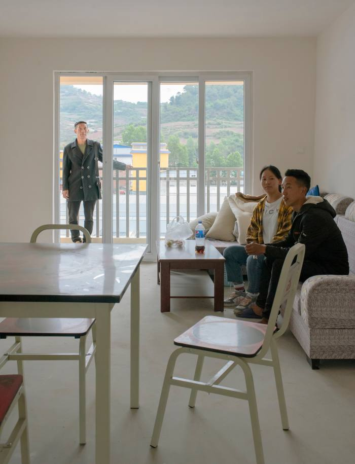 Mou'se Dati with his 17-year-old daughter Lazuo and 25-year-old son Xiongti in their new home. The government provided basic furniture, much of it stamped with: 'People's Government of Sichuan Provincial Committee of the Communist Party of China'