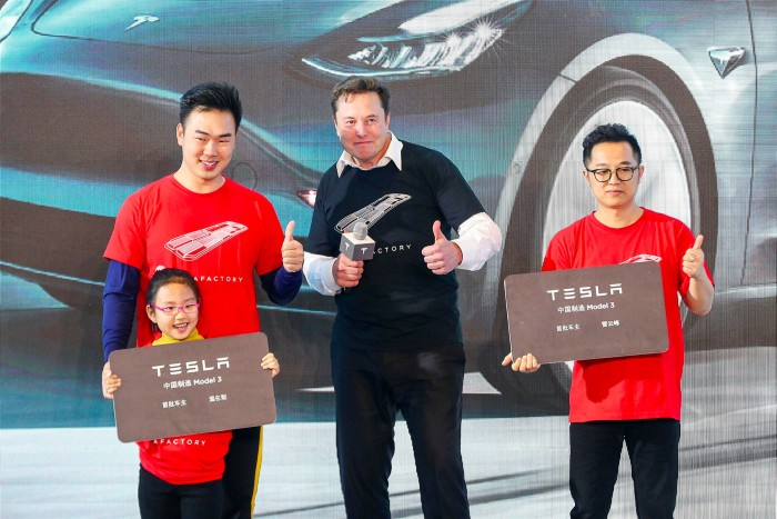 Tesla CEO Elon Musk poses for photos with buyers during the Tesla China-made Model 3 delivery ceremony in Shanghai