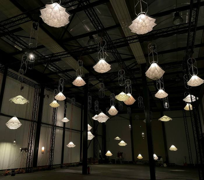 Many elaborate white lampshades hang from a dark ceiling