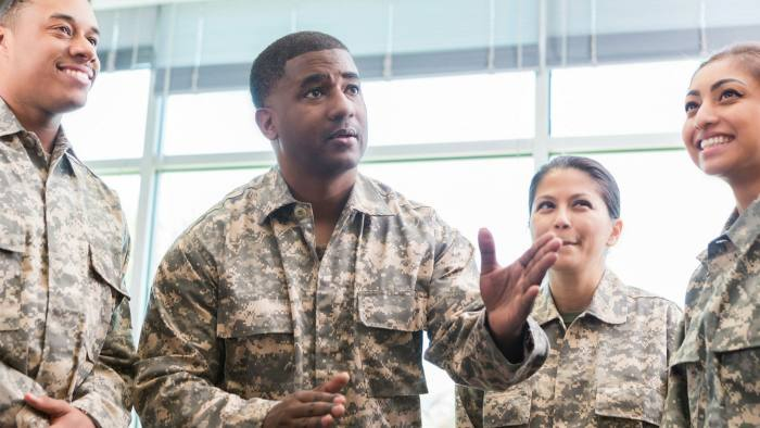 Confident mid adult African American military officer gestures while talking with academy students