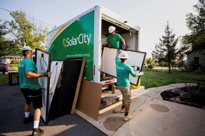 During home installation in New Jersey, SolarCity employees unloaded solar panels from trucks