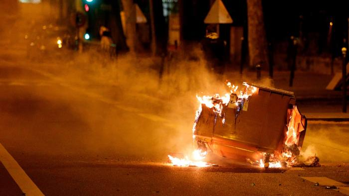 A trash bin burns in the street during clashes in Villeneuve-la-Garenne, a northern suburb of Paris, on Tuesday