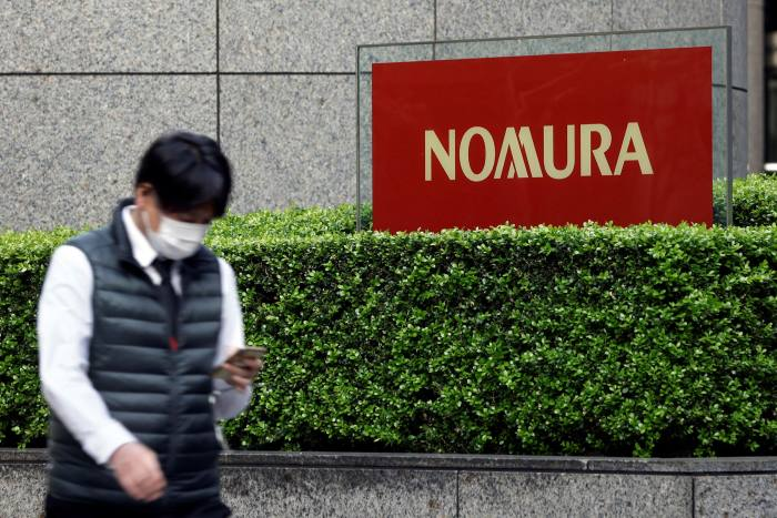 The man walks down the street next to the Nomura sign