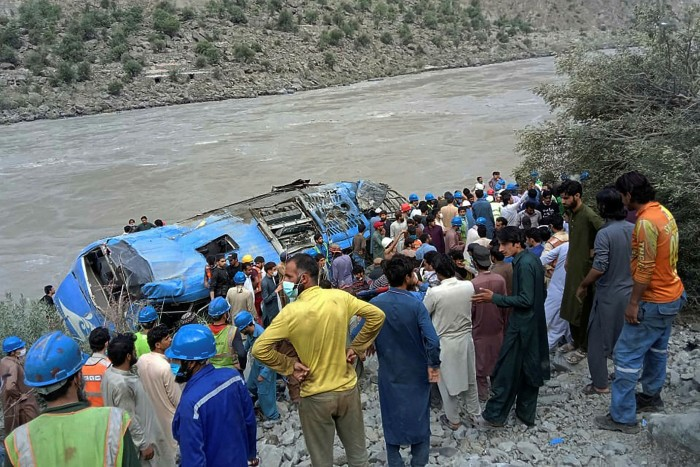 Rescue workers and onlookers gather around a wreck after a bus plunged into a ravine following a bomb explosion, which killed 12 people including 9 Chinese workers, in Kohistan district of Khyber Pakhtunkhwa province on July 14, 2021