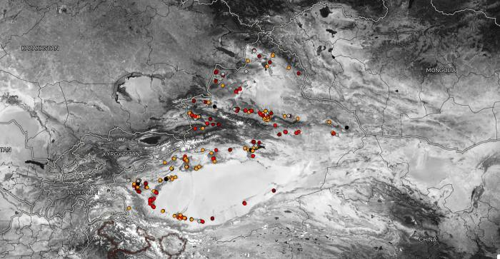 A gray scale map with red dots indicating camps