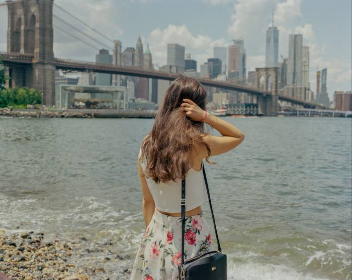 A woman stands on the pebbly bank of the East River and looks out over the water to Lower Manhattan and the Brooklyn Bridge