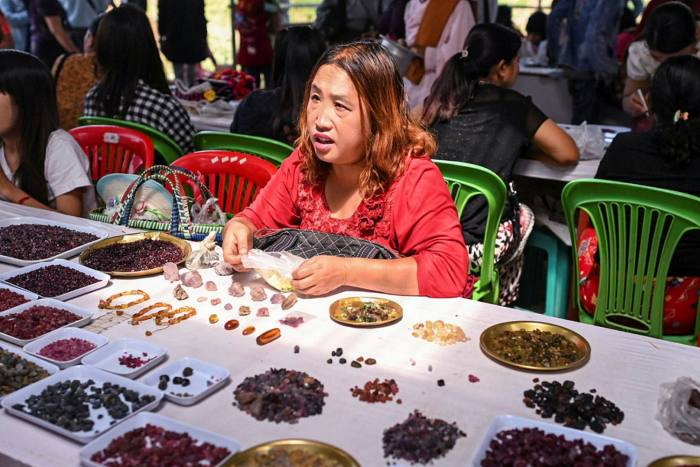 This photo taken on May 17, 2019 shows a seller trading rubies and other gemstones at the gems market in Mogok town, north of Mandalay