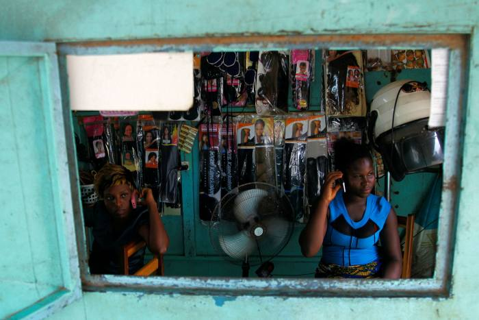 Ivorian women use cellphones in Abidjan. Half of Africans — or just over 500m people — have access to mobile internet coverage but do not use it