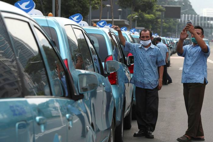 Taxi drivers wait for passengers on the street in Jakarta on May 8, 2020