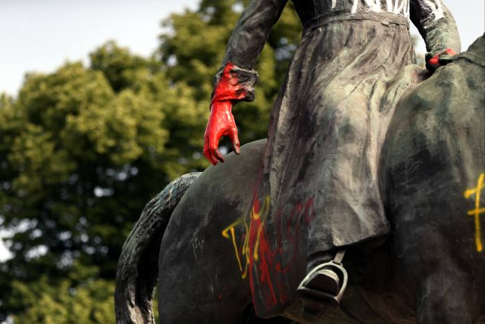 Crimson paint stains the hands of the defaced statue of King Leopold II in Brussels. In June, current monarch Philippe expressed 'deepest regrets' and linked colonialism to racism today