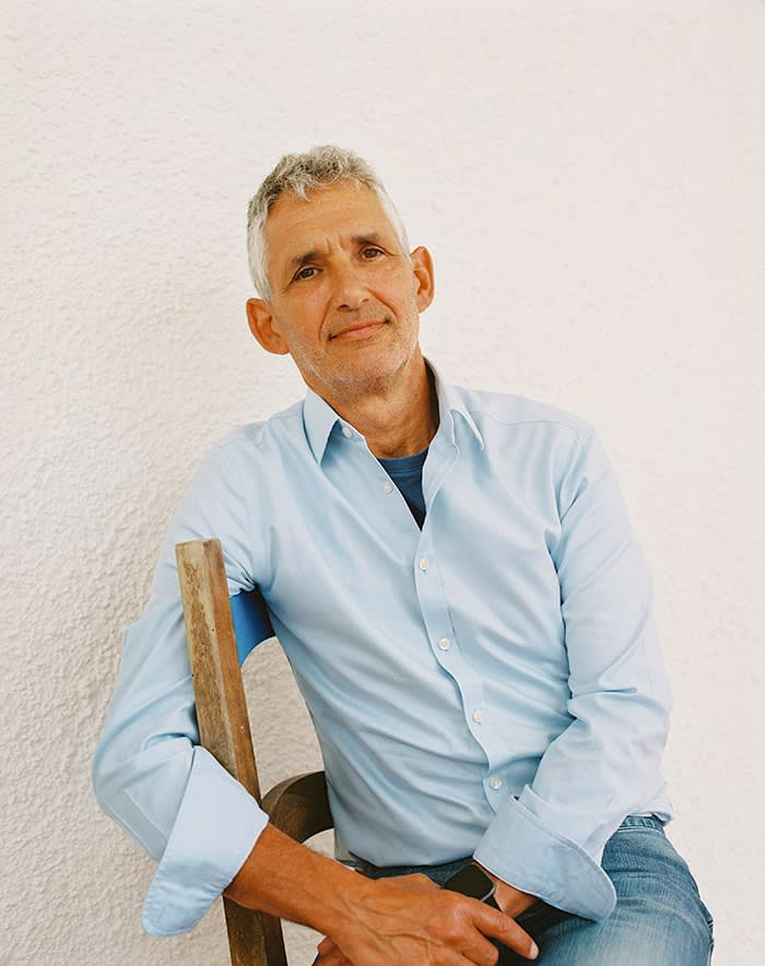 A portrait of Professor Tim Spector, sitting on a chair, wearing a blue shirt and jeans