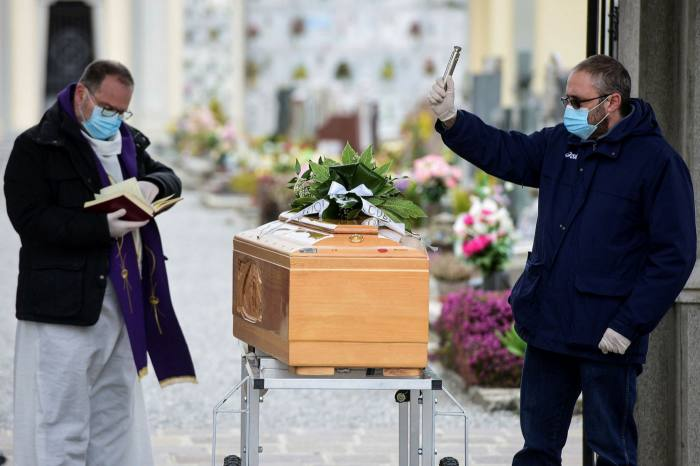 A pallbearer, right, helps a priest give the last blessing to a coffin during a funeral service at the cemetery of Bolgare, Lombardy, on Monday