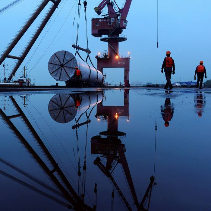 A crane lifts offshore wind energy equipment at a port in Nanjing, Jiangsu province