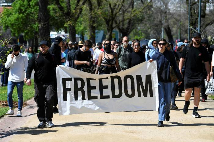 Demonstrators carry a banner reading 'Freedom' during an anti-mandatory vaccination protest in Melbourne