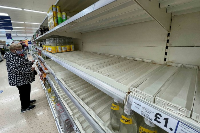 A shopper faces partly empty shelves in a supermarket in London on 30 September