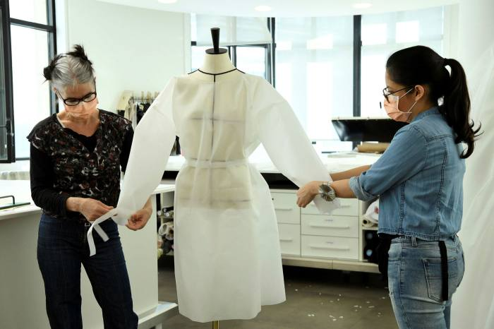 Seamstresses from Louis Vuitton put together a coat jacket for nurses