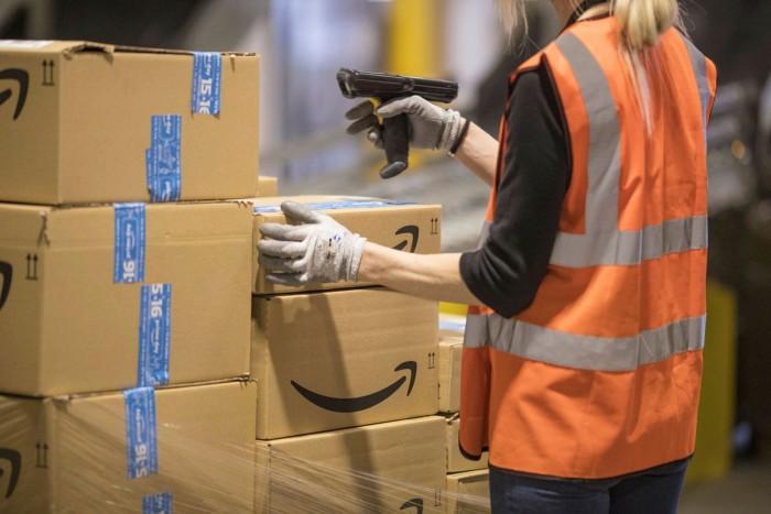 'N Werknemer kontroleer pakkette by die Amazon -vervullingsentrum in Tilbury