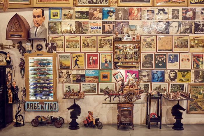 The walls are lined with album covers from musicians including Elvis Presley and Frank Sinatra, and recordings by literary figures such as Pablo Neruda