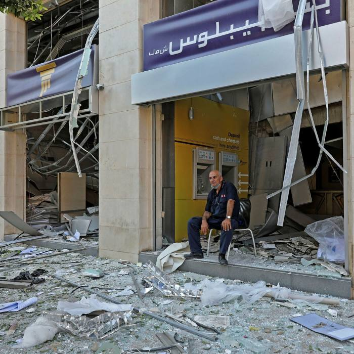 A man sits outside a damaged bank in the aftermath of this week's blast at Beirut's port. Municipal authorities reckon 300,000 people have lost their homes