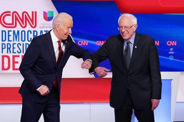 Greeting fellow Democratic presidential hopeful Bernie Sanders for a CNN debate in Washington, March 15. Biden has not adopted Sanders' three key demands – but the Vermont senator has still endorsed him