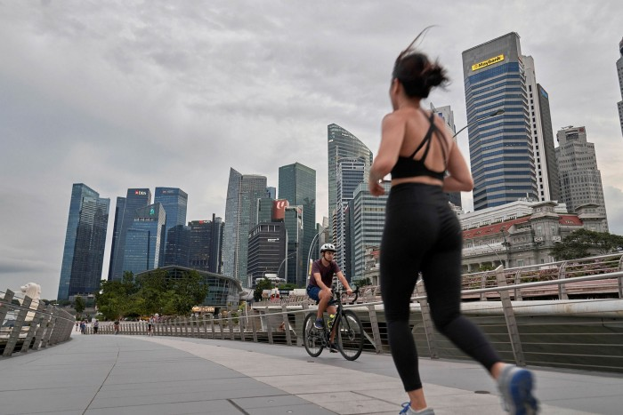 A runner and a cyclist cross the Jubilee Bridge in Singapore as the city state plans to end pandemic-related restrictions