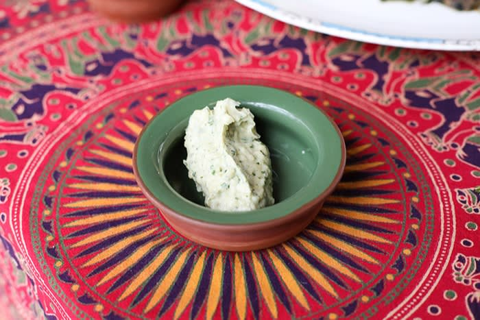 A small bowl on a table contains creamy hilbet dip