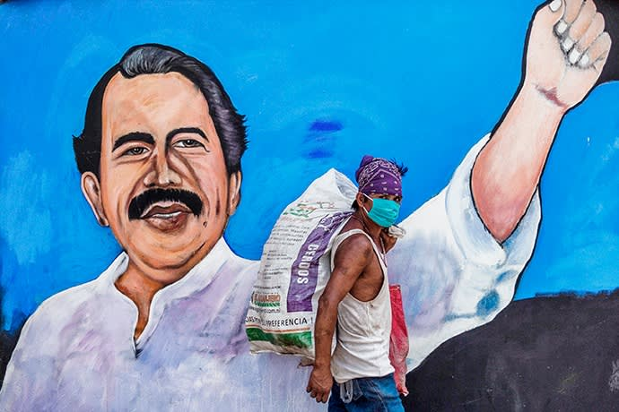 A homeless man wears a face mask against the spread of the new coronavirus, COVID-19, as he walks past a mural depicting Nicaraguan President Daniel Ortega, in Managua on April 9, 2020. - More than 1.46 million cases have been officially recorded and at least 86,289 people have died in 192 countries since the virus emerged in China in December, according to an AFP tally at 1900 GMT Wednesday based on official sources. (Photo by INTI OCON / AFP) (Photo by INTI OCON/AFP via Getty Images)