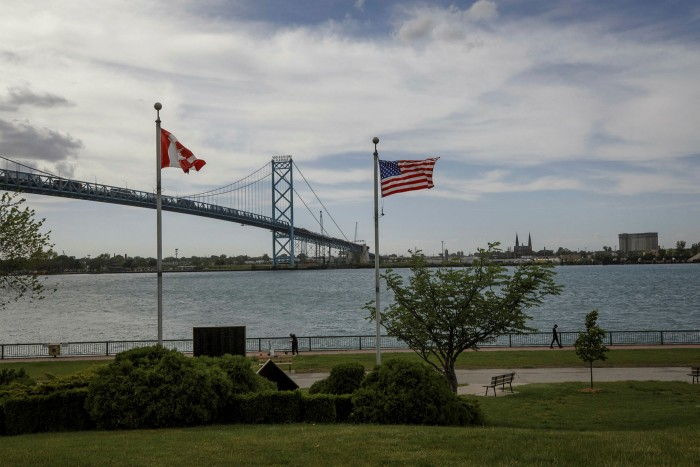 US and Canadian flags fly near the Ambassador Bridge connecting Detroit with Windsor, Ontario