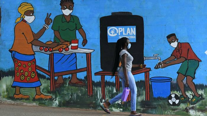A woman walks past graffiti that promotes hand washing and face masks in Kibera, Nairobi. Critics say that debt relief efforts to help poor nations cope with the pandemic are underwhelming.