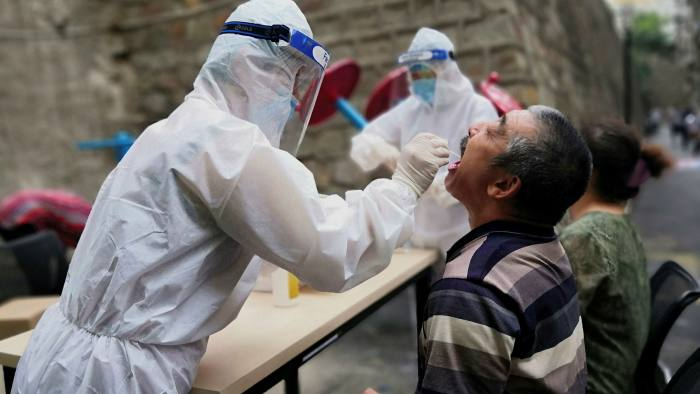 A medical worker in protective suit collects a sample from a man during a coronavirus testing for residents in Urumqi, Xinjiang province on July 19