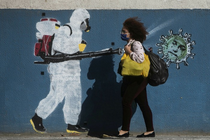 A woman walks past graffiti depicting a cleaner spraying viruses with the face of President Bolsonaro in Estacio neighborhood in Rio de Janeiro
