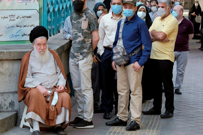 A cleric waits with local people  outside a polling station in Tehran on June 18