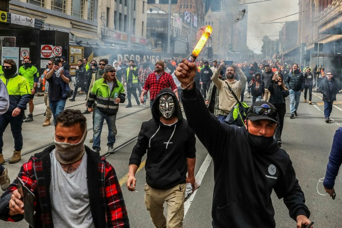Protesters are seen marching as a torch burns as thousands march through Melbourne