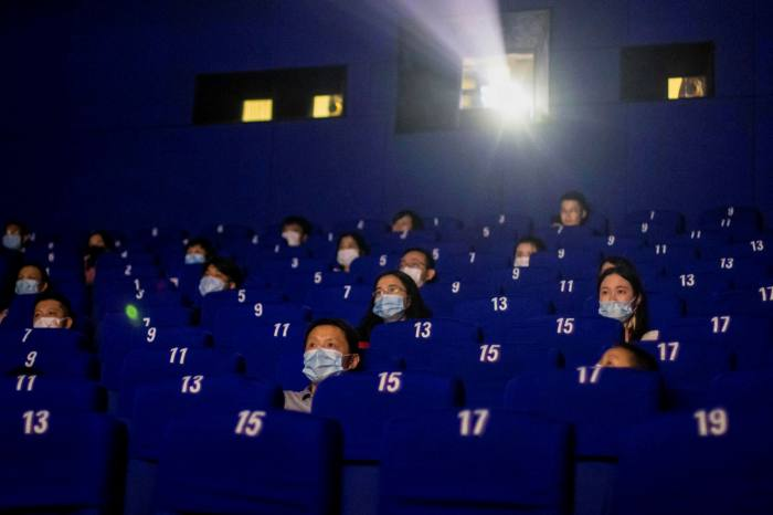 People wearing face masks and observing social distancing while watching a movie at a cinema in Shanghai