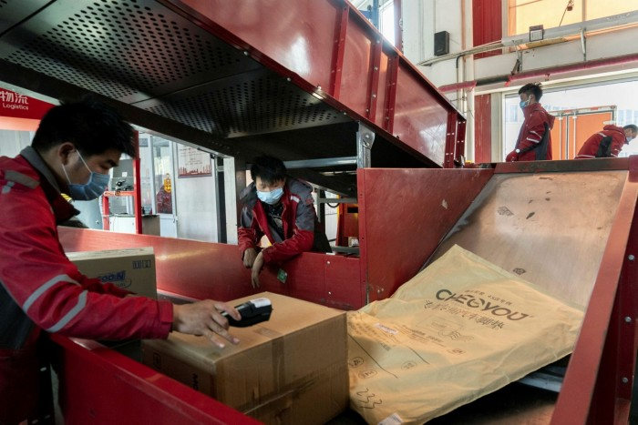 Employees wearing protective masks sort parcels at a JD.com