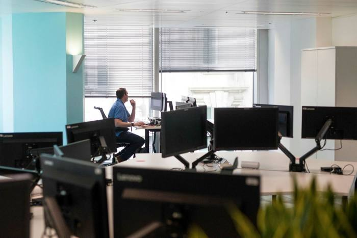 An employee works at a desk during the first phase of the reoccupation of offices in London in June