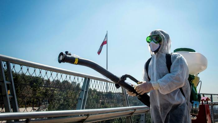 A firefighter wearing protective clothing, mask and goggles, sprays disinfectant on Tabia't bridge pedestrian overpass in Tehran, Iran, on Monday, March 9, 2020.
