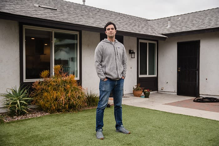 Mike Gnoffo standing on a lawn in front of a one-storey house