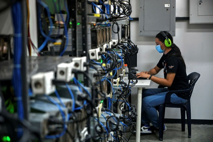 An employee works a bitcoin mining centre in Venezuela, where coins such as Dash get used more for smaller purchases, bitcoin for larger ones because of higher fees, and litecoin for things like paying satellite bills