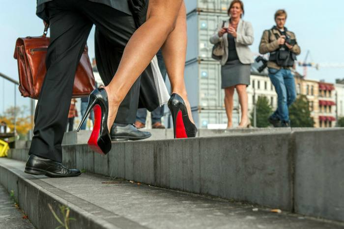 A woman steps on high heels with red soles on the steps