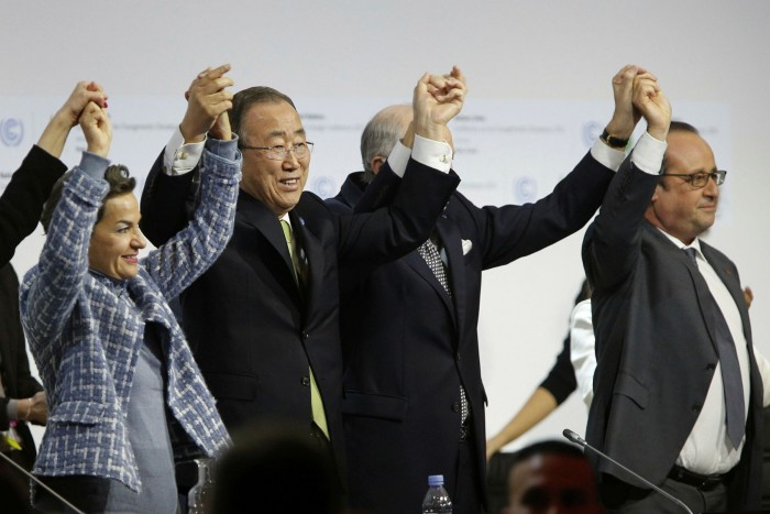 From left: executive secretary of the United Nations Framework Convention on Climate Change Christiana Figueres, secretary general of the United Nations Ban Ki Moon, foreign affairs minister and president-designate of COP21 Laurent Fabius, and France's president Francois Hollande raise hands together after adoption of the global warming pact at the COP21 Climate Conference in Le Bourget, north of Paris, in December 2015