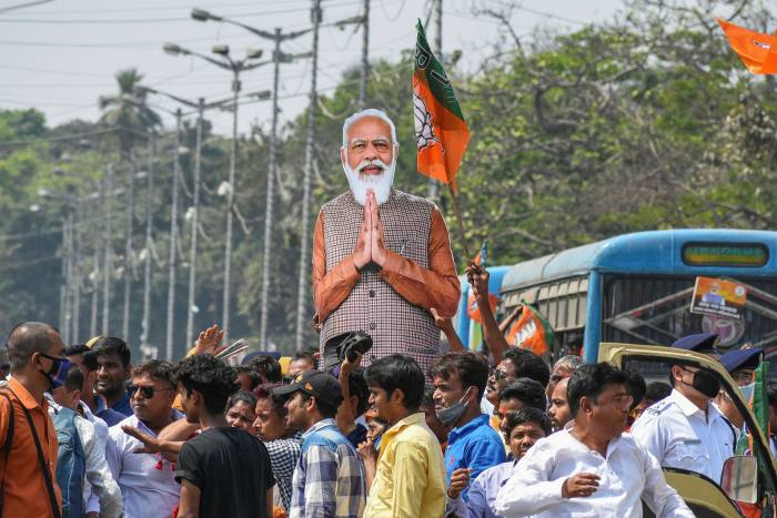 Supporters of Modi's ruling BJP party carry a cut-out of the prime minister at a campaign rally in March