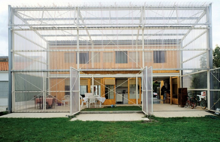A two-story house with a flat roof sits in a large translucent structure